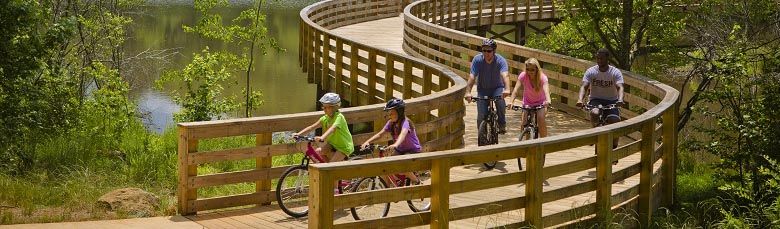 Image of five people cycling across a wooden bridge